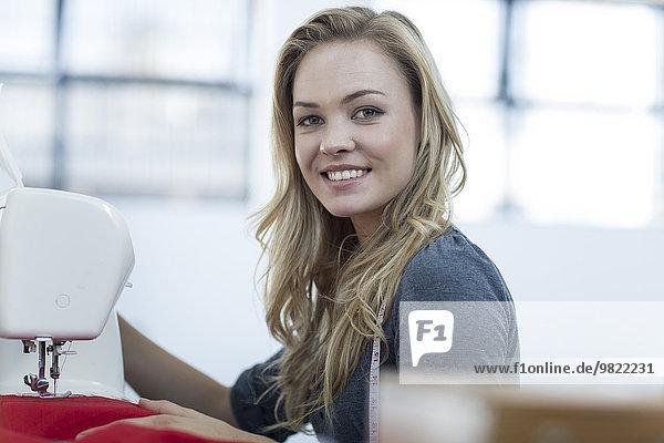 Porträt einer lächelnden jungen Frau bei der Arbeit mit einer Nähmaschine