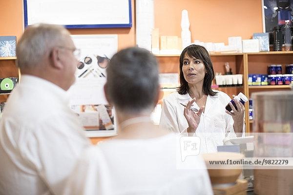 Apothekerin im Gesundheitsgeschäft berät Seniorenpaar