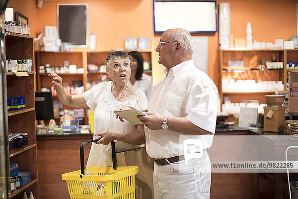 Seniorenpaar mit digitalem Tablett im Gesundheitsshop