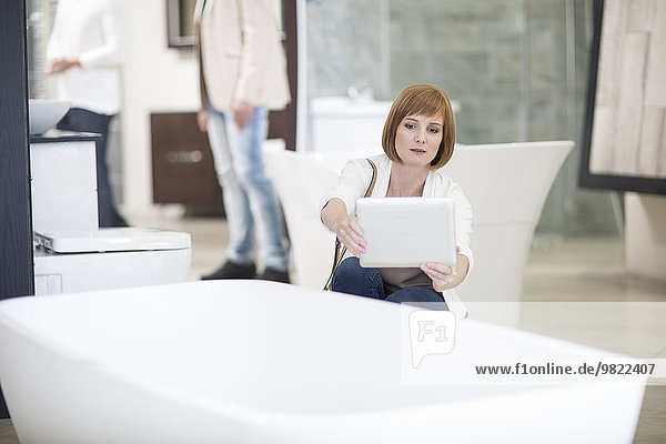 Frau beim Fotografieren einer Badewanne mit ihrem digitalen Tablett in einem Badezimmergeschäft