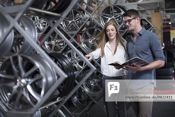 Mann und Frau im Reifengeschäft treffen eine Auswahl für einen Verkauf