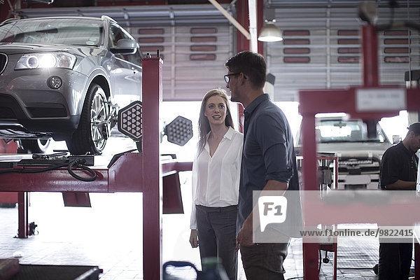 Mann zeigt der Kundin den Prozess der Reifenmontage