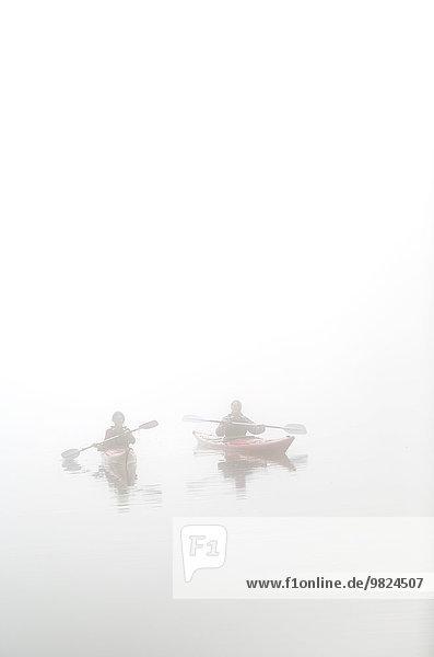 People kayaking in fog