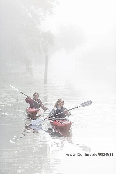 Women kayaking in fog
