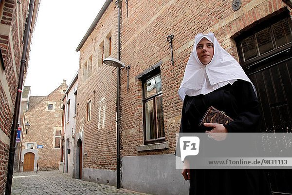 Belgium  Flanders  Limbourg province  historic city of Tongeren (Tongres)  young lady dressed as a nun in the Beginage (ancient quarter of the beguines)