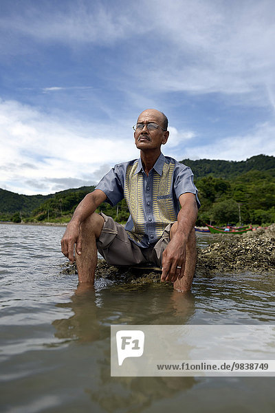 Alter Mann blickt auf das Meer  dem beim Tsunami 2004 fast seine gesamte Familie zum Opfer gefallen ist  Dorf Lam Rukam  Subdistrict Rozma  Aceh  Sumatra  Indonesien  Asien