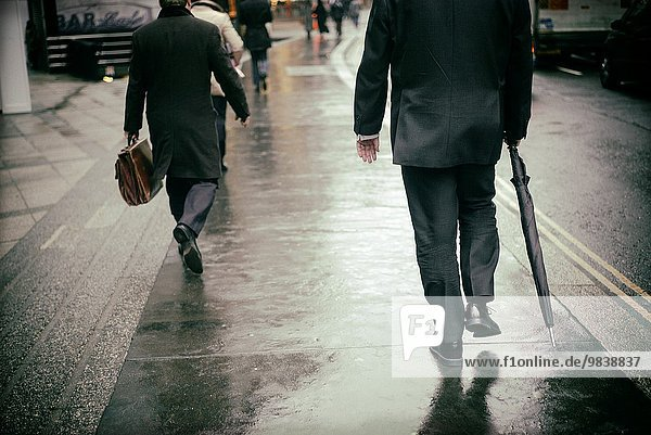 Back view of two man  walking in the street  One with an umbrela and the other one With an old briefcase  in London  England  UK  Europe.