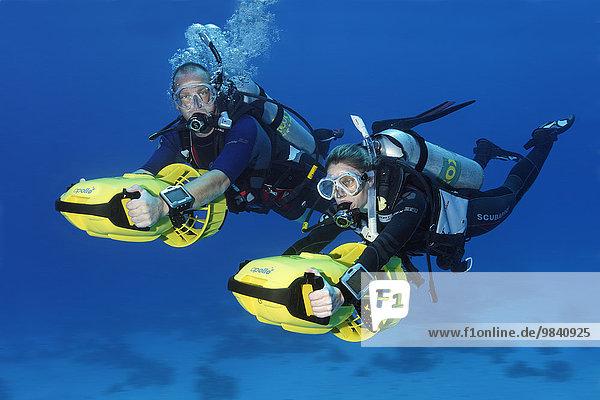 Taucher mit Scooter Unterwasserfahrzeug erkunden Korallenriff,  Soma Bay,  Hurghada,  Ägypten,  Rotes Meer,  Afrika