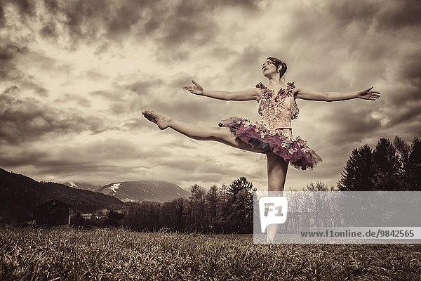 Ballerina mit Tutu tanzt vor wolkigem Himmel Ballerina mit Tutu tanzt vor wolkigem Himmel