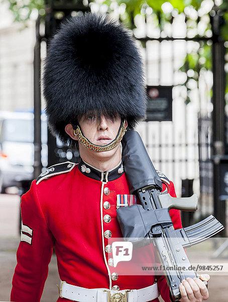 Wachmann der königlichen Garde mit Bärenfellmütze und Gewehr beim Wachwechsel  Wachablösung  London  England  Großbritannien  Europa