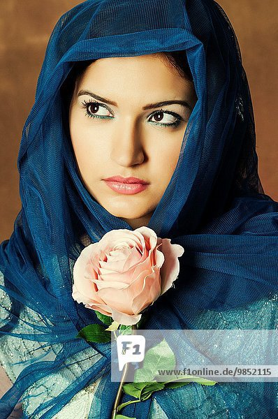 Veiled young woman with a pink rose.