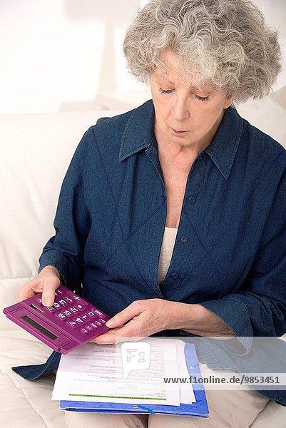 Interior zu Hause Senior Senioren Frau Schönheit Papier Taschenrechner halten vorlesen