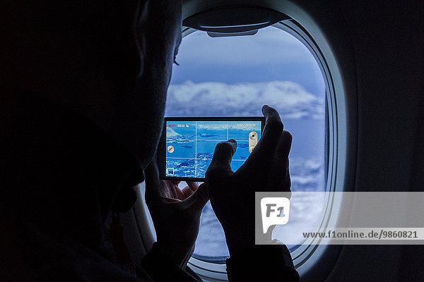 Silhouette eines Mannes  der Fotos von Bergen mit einem Smartphone aus einem Flugzeugfenster schießt