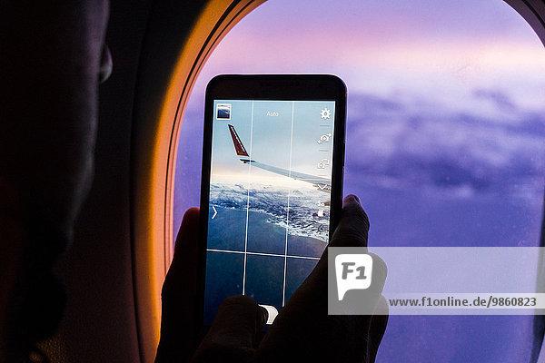 Silhouette eines Mannes  der Fotos von Bergen und einem Flugzeugflügel mit einem Smartphone aus einem Flugzeugfenster schießt