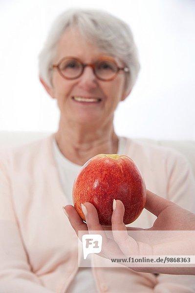 Senior Senioren Frau Schönheit Angebot Hintergrund rot Fokus auf den Vordergrund Fokus auf dem Vordergrund Apfel Bewegungsunschärfe