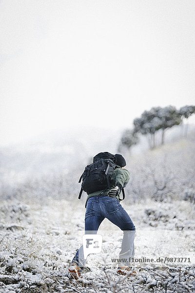 A man running up a slope in the mountains carrying a rucksack.