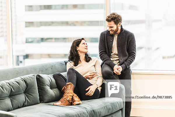 Zwei Personen  eine Frau  die auf einem Sofa sitzt und die Füße entspannt nach oben streckt  und ein Mann  der zu ihr sitzt und mit ihr spricht.