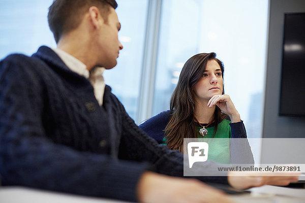 Ein Mann und eine Frau  die bei einer Sitzung in einem Büro sitzen.