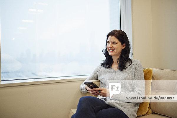 Eine Geschäftsfrau sitzt an einem Fenster und hält ein Smartphone in der Hand.
