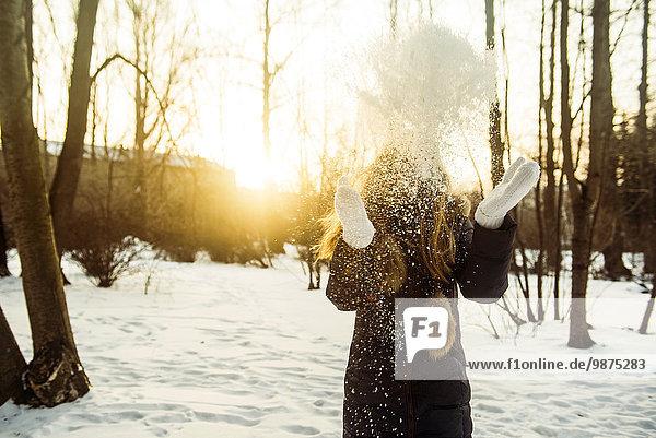 Caucasian woman playing in snowy field