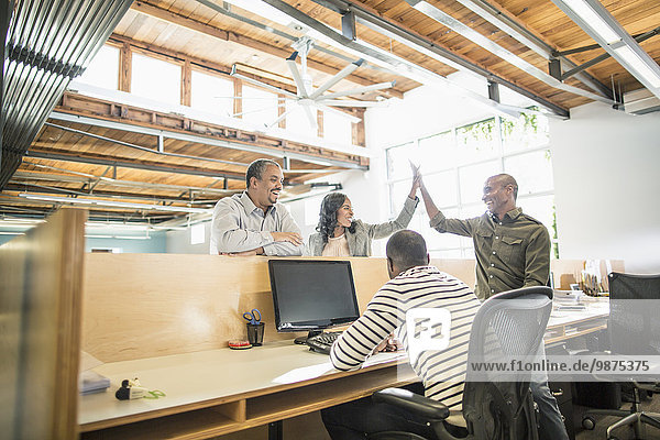 Business people celebrating at desk in office