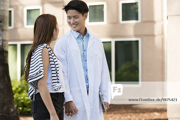 Korean doctor walking with girlfriend outdoors