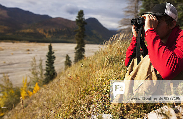 Man watches a braided riverbed with binoculars while hunting near Tok  Southcentral Alaska