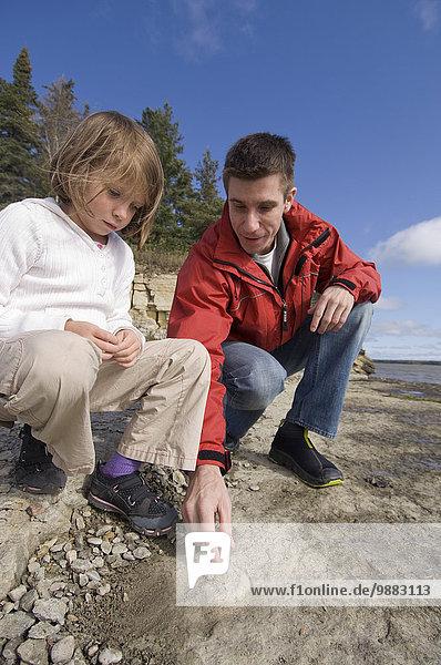 Wasserrand stehend Menschlicher Vater unterhalb See Meer Insel jung Tochter Hecla-Grindstone Provincial Park Kalkstein Million