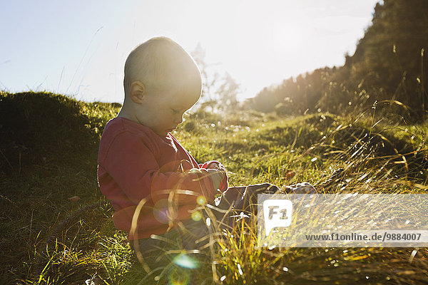 Baby girl sitting in field touching blades of grass