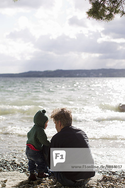 Father and baby daughter crouching on lakeside  Lake Starnberg  Bavaria  Germany