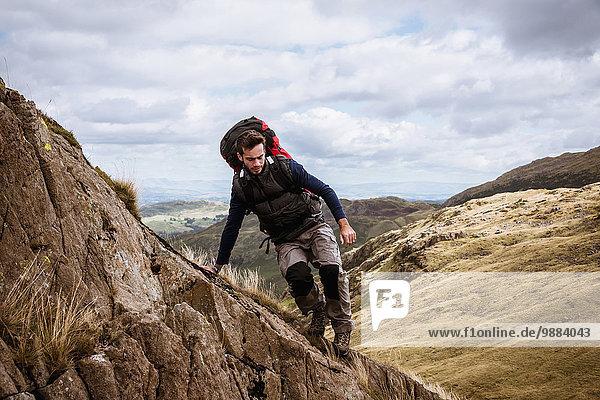 Junge männliche Wanderer  die aus dem Felsen steigen  The Lake District  Cumbria  UK