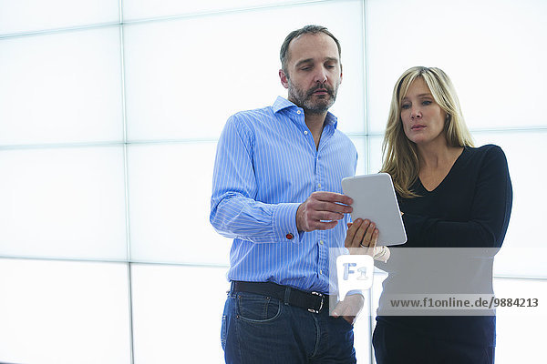 Mann und Frau mit digitalem Tablett gegen hinterleuchtete Wandpaneele
