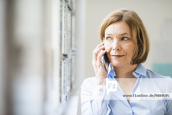 Mature businesswoman looking out of office window and chatting on smartphone