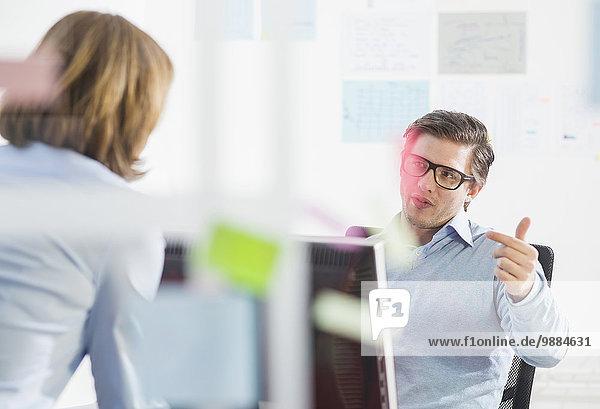 Geschäftsmann und Frau im Gespräch am Schreibtisch