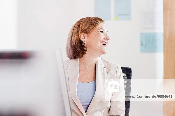 Reife Geschäftsfrau lacht am Schreibtisch