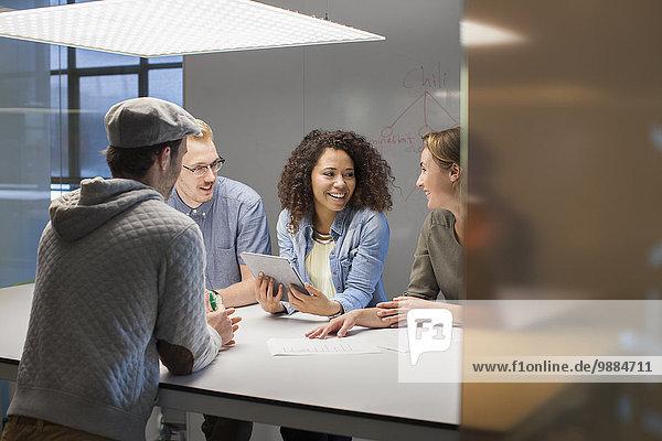 Vier kreative Kollegen treffen sich am Konferenztisch
