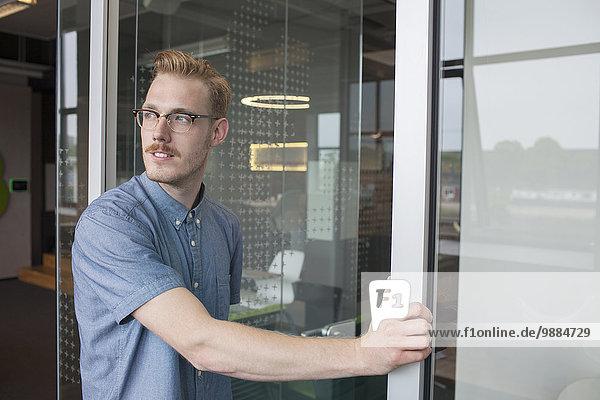 Junger Mann schaut über die Schulter von der Bürotür aus Junger Mann schaut über die Schulter von der Bürotür aus