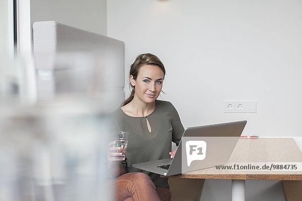 Porträt einer jungen Frau mit Laptop im Büro Porträt einer jungen Frau mit Laptop im Büro