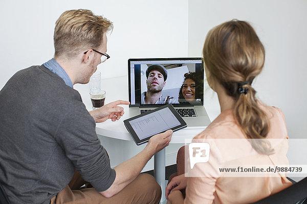 Kollegen teilen Laptop-Videoanrufe mit Partnern
