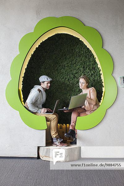 Designerinnen und Designer arbeiten an Laptops in baumförmigen Büroräumen Designerinnen und Designer arbeiten an Laptops in baumförmigen Büroräumen