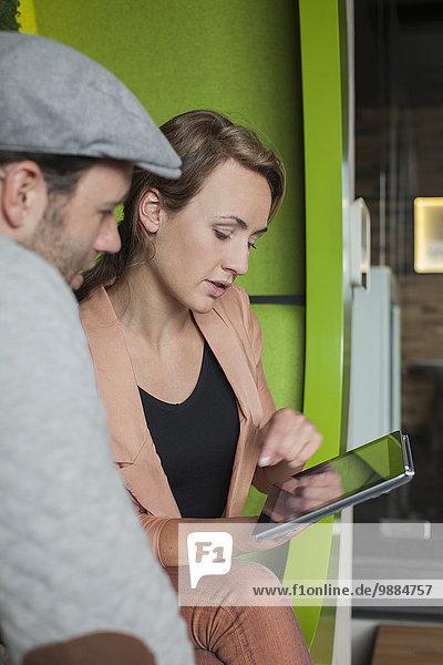 Designerinnen und Designer arbeiten an digitalen Tabletts in Büroräumen Designerinnen und Designer arbeiten an digitalen Tabletts in Büroräumen