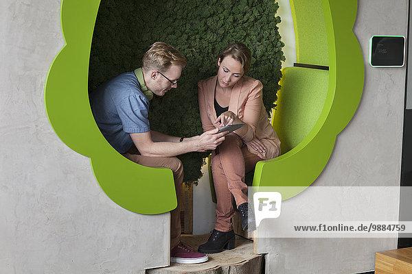 Designerinnen und Designer arbeiten an digitalen Tabletts in baumförmigen Büroräumen Designerinnen und Designer arbeiten an digitalen Tabletts in baumförmigen Büroräumen