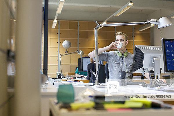 Junger Mann trinkt Kaffee am Schreibtisch Junger Mann trinkt Kaffee am Schreibtisch