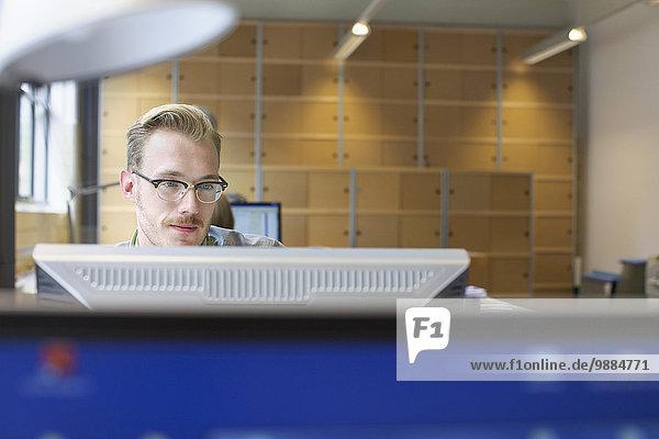 Junger Mann mit Computer am Schreibtisch