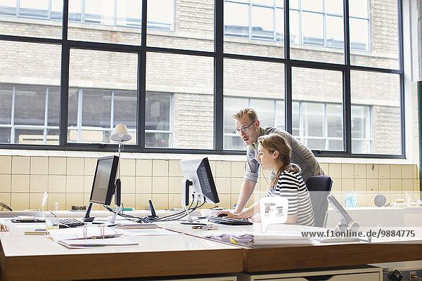 Kollegen  die sich informell am Schreibtisch treffen.