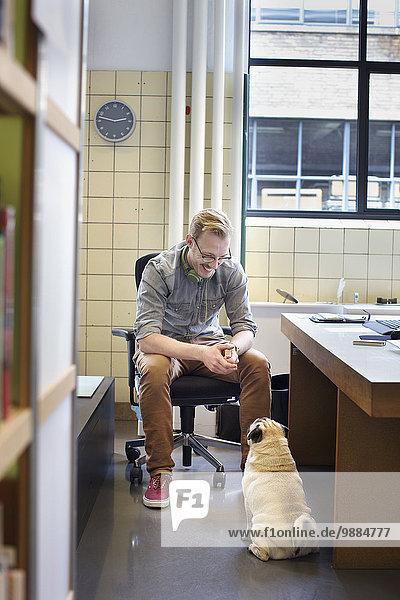 Junger Mann schaut vom Schreibtisch auf den süßen Hund herab.