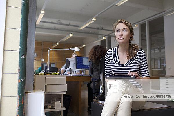 Junge Frau mit digitalem Tablett im Büro