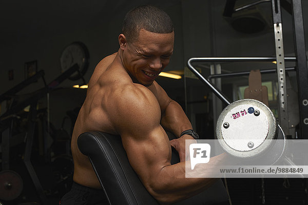 Mid adult man  lifting weights