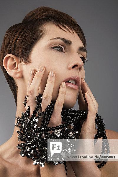 Studio-Porträt einer Frau mit schwarzen Perlen zwischen den Fingern