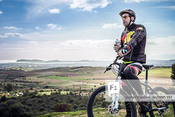 Männlicher Mountainbiker mit Wasserflasche am Küstenweg  Cagliari  Sardinien  Italien